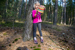 Cute little blond girl with wicker basket posing at forest. Cute little child girl with wicker basket posing and walking through the woods. Summer holiday Stock Photography