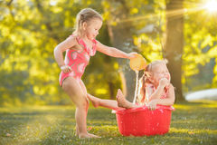 The cute little blond girls playing with water splashes on the field in summer Royalty Free Stock Images