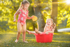 The cute little blond girls playing with water splashes on the field in summer Stock Image