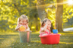 The cute little blond girls playing with water splashes on the field in summer Stock Images