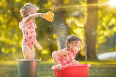 The cute little blond girls playing with water splashes on the field in summer Royalty Free Stock Photography