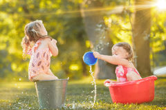 The cute little blond girls playing with water splashes on the field in summer Stock Photography
