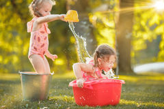 The cute little blond girls playing with water splashes on the field in summer Royalty Free Stock Photo