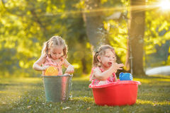 The cute little blond girls playing with water splashes on the field in summer Stock Photo