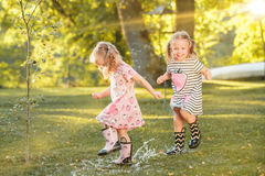 The cute little blond girls in rubber boots playing with water splashes on the field in summer Stock Image