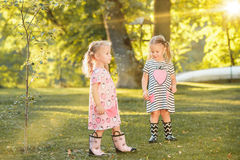 The cute little blond girls in rubber boots playing with water splashes on the field in summer Stock Photography