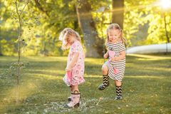 The cute little blond girls in rubber boots playing with water splashes on the field in summer Royalty Free Stock Image