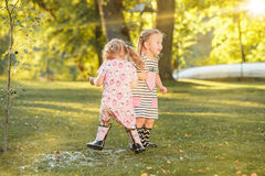 The cute little blond girls in rubber boots playing with water splashes on the field in summer Royalty Free Stock Images