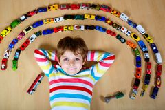 Cute little blond kid boy playing with lots of toy cars indoor. Stock Photos