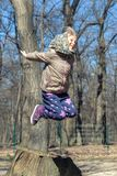 Cute little blond kid girl having fun outdoors. Child in casual sport wear and kerchief jumping high from tree stump in forest stock images