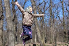 Cute little blond kid girl having fun outdoors. Child in casual sport wear and kerchief jumping high from tree stump in forest royalty free stock photos