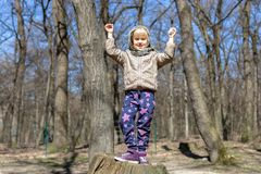 Cute little blond kid girl having fun outdoors. Child in casual sport wear and kerchief jumping high from tree stump in forest stock image