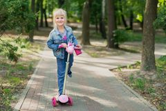 Cute little blond kid girl riding scooter in city park. Preschooler girl in jeans overall having fun during outdoor sport. Activities. Summer leisure and stock photo