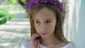 Cute little blonde with flower`s crown on the head looks at camera. Slowly.  stock video