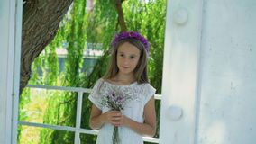 Cute little blonde with flower`s crown on the head smiling at camera. Slowly.  stock video