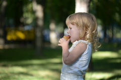 Cute little blonde girl is backlit against the background of. A little girl with blond hair in a park eating ice cream Royalty Free Stock Images