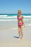 Cute little blonde girl on beach. Little happy blond caucasian girl child in pink swimwear playing in the sean and having great holiday fun Royalty Free Stock Image