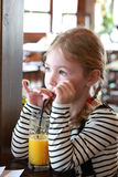 Cute little blonde girl drinks orange juice using drinking straw Stock Photography
