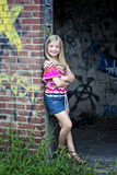 Cute little blonde girl at graffiti wall stock images