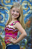 Cute little blonde girl at graffiti wall stock photo