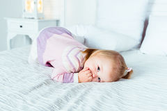 Cute little blonde girl on hands and knees on white bed Royalty Free Stock Photos