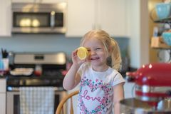 Cute little girl in the kitchen. Cute little blonde girl having fun in the kitchen holding up a lemon slice Stock Photography