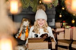 Cute little blonde girl having a gift in her hands on a christmas background. Happy family concept. Stock Images