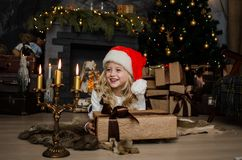 Cute little blonde girl having a gift in her hands on a christmas background. Happy family concept. Royalty Free Stock Image