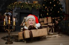 Cute little blonde girl having a gift in her hands on a christmas background. Happy family concept. Stock Image