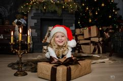 Cute little blonde girl having a gift in her hands on a christmas background. Happy family concept. Stock Photos
