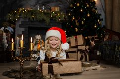 Cute little blonde girl having a gift in her hands on a christmas background. Happy family concept. Cute little blonde girl having a gift in her hands on a Stock Images