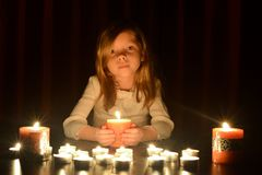 The cute little blonde girl is holding a burning candle, lots of candles are around her over dark background. stock photo