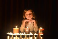 The cute little blonde girl keeps her hands under the chin. Lots of candles are around her, over dark background stock photography
