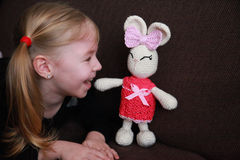 Cute little blonde girl laughing at easter crochet bunny Royalty Free Stock Images
