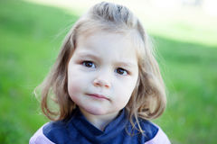 Cute little blonde girl looking at camera Stock Image