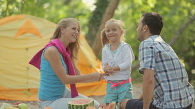 Cute little blonde girl with parents outdoors with stock footage