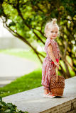 Cute little blonde girl in a pink jumpsuit holding a basket in h stock image