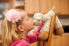 Cute little blonde girl plays with sheep toy in livingroom Royalty Free Stock Image