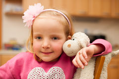 Cute little blonde girl plays with sheep toy in livingroom Royalty Free Stock Photos