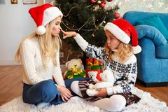 Cute little blonde girl in Santa`s hat touching mothers nose, ho Royalty Free Stock Images