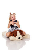 Cute little blonde girl sitting on a big soft dog Stock Images