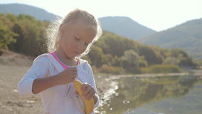 A cute little blonde girl standing on the shore of. The lake and trying to open a banana near the forest and mountains stock video footage