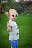 Cute little blonde girl with sunglases posing in a summer green park - portrait Stock Photo