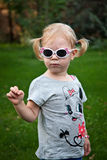 Cute little blonde girl with sunglases posing in a summer green park - portrait Royalty Free Stock Image