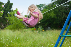 Cute little blonde girl on a swing Royalty Free Stock Images