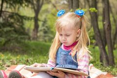 Cute little blonde girl with two ponytails relaxing with a book. And a bun in the city park on a spring sunny day Stock Photo