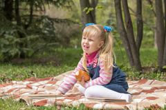 Cute little blonde girl with two ponytails relaxing with a book. And a bun in the city park on a spring sunny day Royalty Free Stock Images