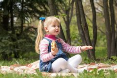 Cute little blonde girl with two ponytails relaxing with a book. And a bun in the city park on a spring sunny day Stock Photography