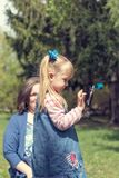 Cute little blonde girl with two ponytails taking selfie in the. City park on a spring sunny day Royalty Free Stock Photo