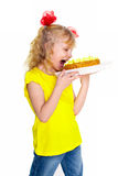 Cute little blonde girl wants to eat cake, isolated on a white background Royalty Free Stock Photo